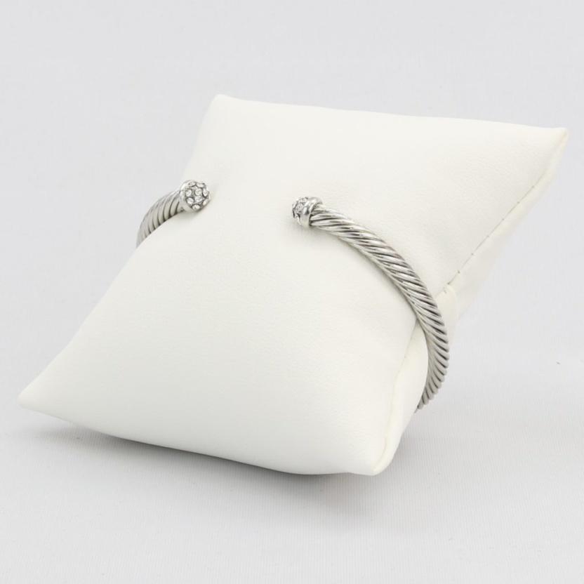 Twisted cable cuff bracelet capped with diamond-like cubic zirconia gems