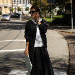 Black pleated skirt and jacket with white top and shoes