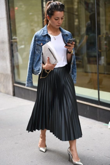 Blue denim jacket over neutral top and black pleated skirt