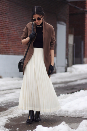 Camel coat with black turtleneck and white pleated skirt