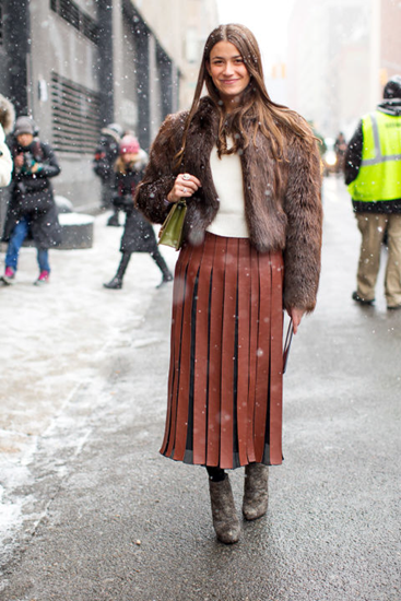 Fur coat adds layers and color to pleated skirt outfit