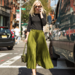 Green pleated skirt with green purse black top
