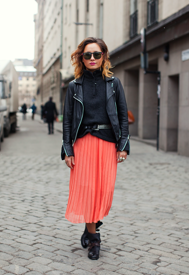 Living coral pleated skirt with edgy black top and leather jacket