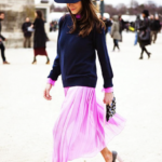 Neon pink pleated skirt and top with dark sweater and hat