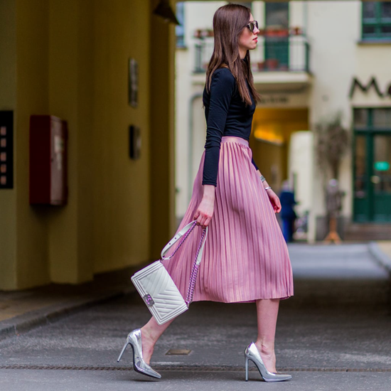 Pink pleated skirt with black top and color popping purse