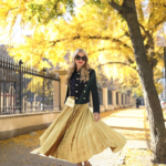 Yellow pleated skirt with black top and gold accessories