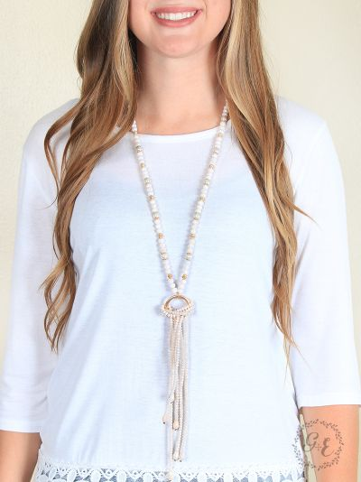 Elegant Ivory Beaded Tassel Necklace with Gold Ring Accent on model