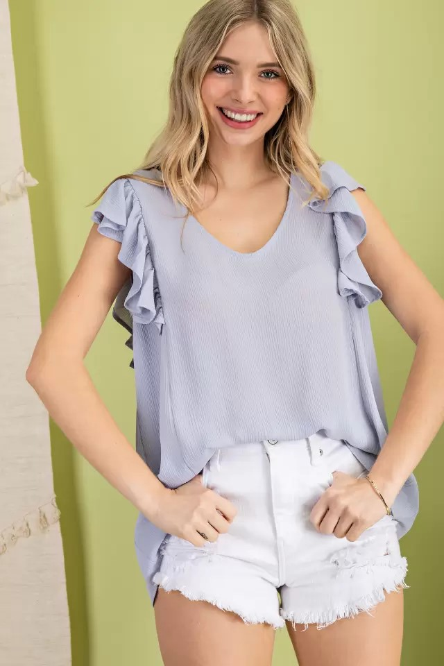 Sleeveless ruffle V-neck woven blouse silver blue front hands in pocket